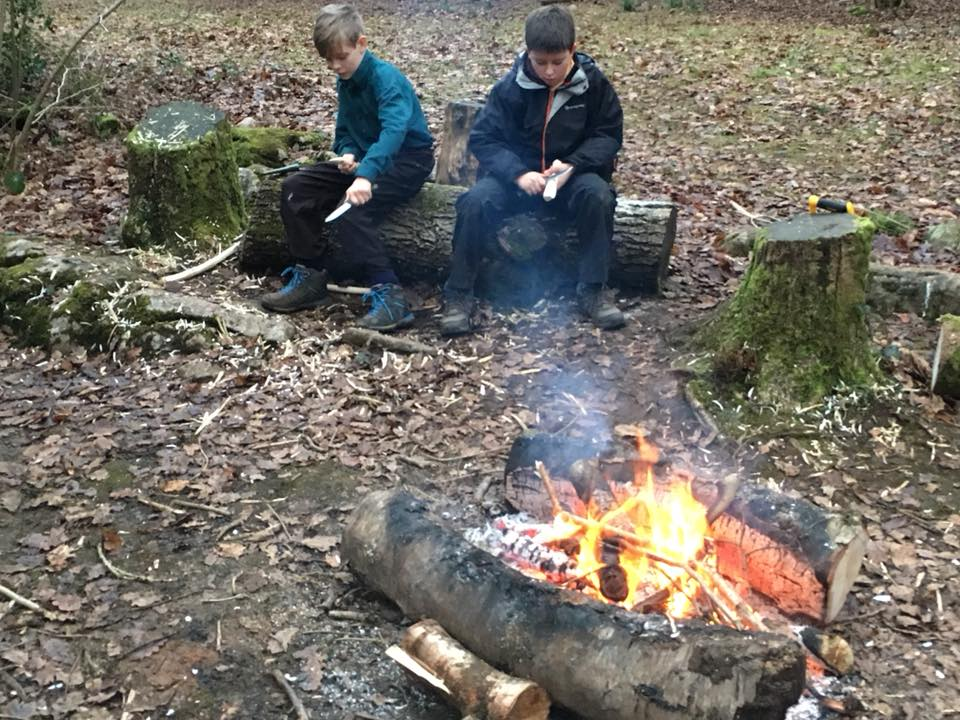 Scouts whittling around a fire.