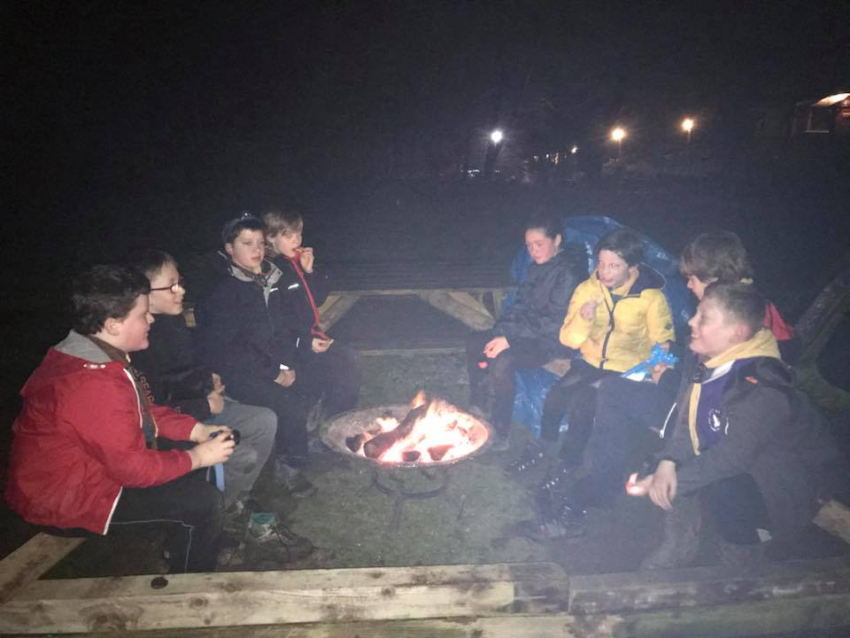Scouts around a campfire at night